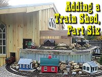Putting the walls and windows on our garden railway train shed.  Click to go to article.