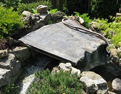 A scrap of pond liner or heavy landscaping plastic will keep dirt, etc., from leaking through onto the tracks.  Click for bigger photo.