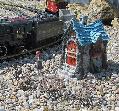 A resin fairy garden house, a metal fairy garden bistro set, a handpainted Chinese figure glued to PETE, and a Lionel toy train.  Click for a much bigger photo.